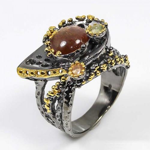 טבעת עבודת יד בשיבוץ אבני סנסטון וספיר כסף ציפוי זהב ורודיום שחור